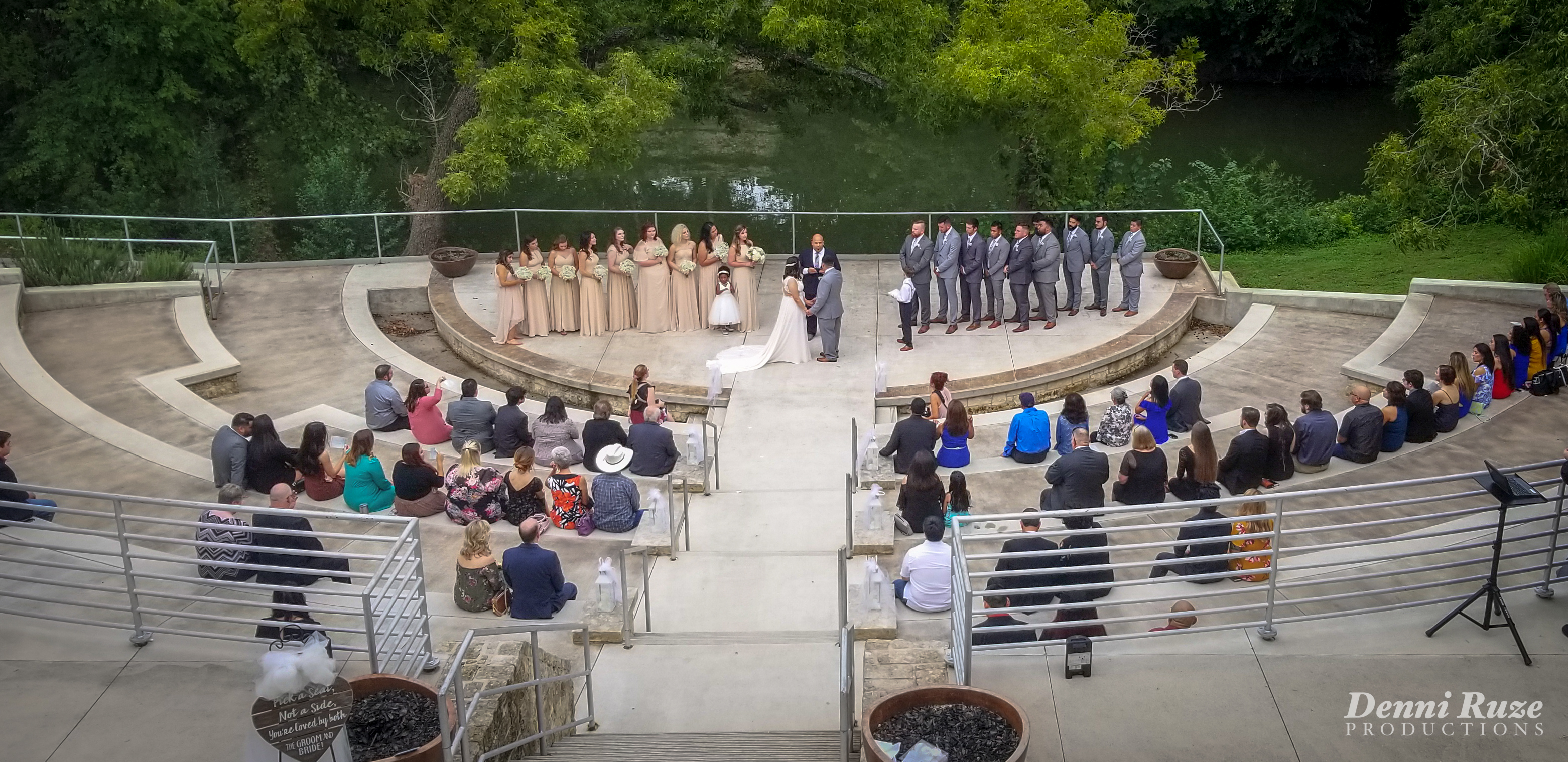 The wedding ceremony, with the bridal party on stage and the bride and groom listening to the minister. Guests are seated, with green foliage and river in the background.